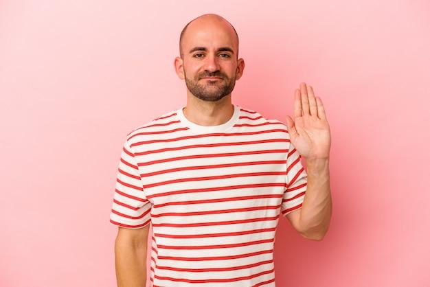 Jeune homme chauve caucasien isolé sur fond rose souriant joyeux montrant le numéro cinq avec les doigts.