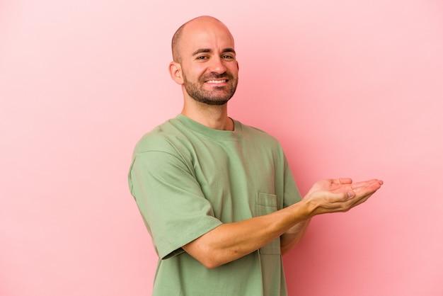 Jeune homme chauve caucasien isolé sur fond rose tenant un espace de copie sur une paume.