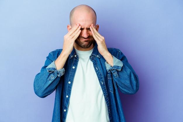 Jeune homme chauve caucasien isolé sur fond violet ayant mal à la tête, touchant l'avant du visage.
