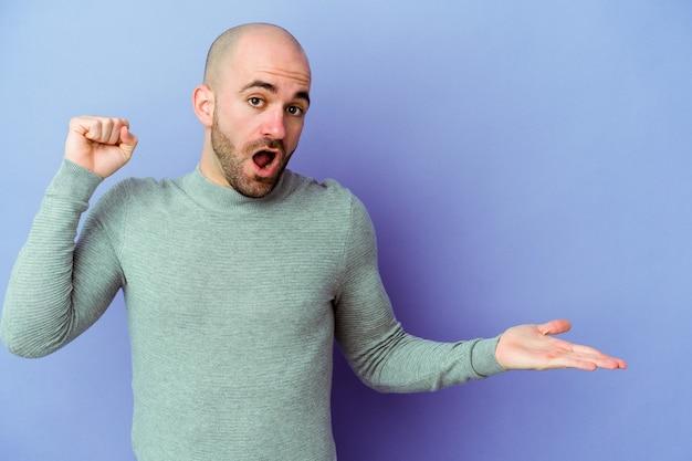 Jeune homme chauve caucasien isolé sur fond violet détient un espace de copie sur une paume, gardez la main sur la joue. émerveillé et ravi.
