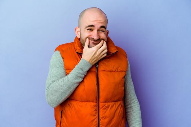 Jeune homme chauve caucasien isolé sur fond violet doutant entre deux options.