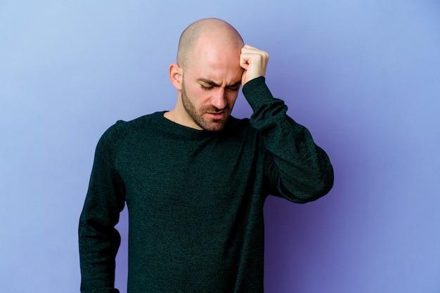Jeune homme chauve caucasien isolé sur fond violet fatigué et très endormi en gardant la main sur la tête.