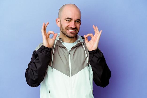 Jeune homme chauve caucasien isolé sur fond violet gai et confiant montrant un geste ok.