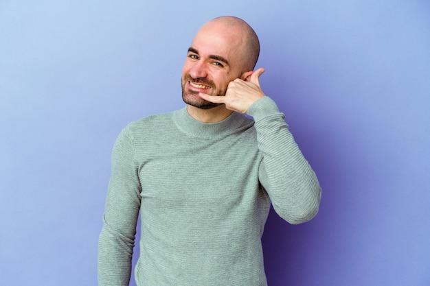 Jeune homme chauve caucasien isolé sur fond violet montrant un geste d'appel de téléphone mobile avec les doigts.