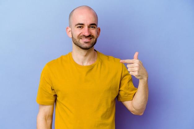 Jeune homme chauve caucasien isolé sur fond violet personne pointant à la main vers un espace de copie de chemise, fier et confiant