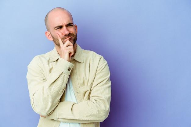 Jeune homme chauve caucasien isolé sur fond violet regardant de côté avec une expression douteuse et sceptique.