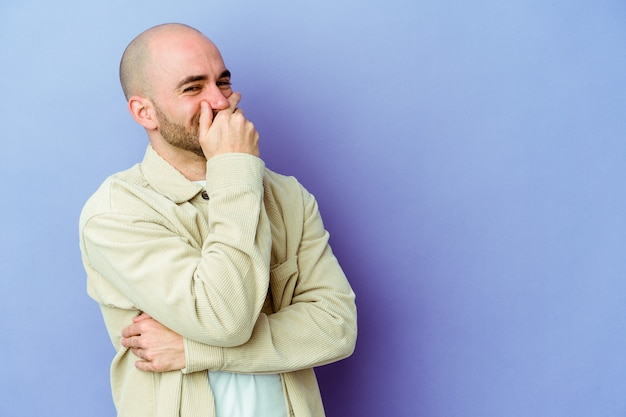 Jeune homme chauve caucasien isolé sur fond violet riant heureux, insouciant, émotion naturelle.