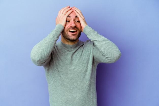 Jeune homme chauve caucasien isolé sur fond violet rit joyeusement en gardant les mains sur la tête. concept de bonheur.