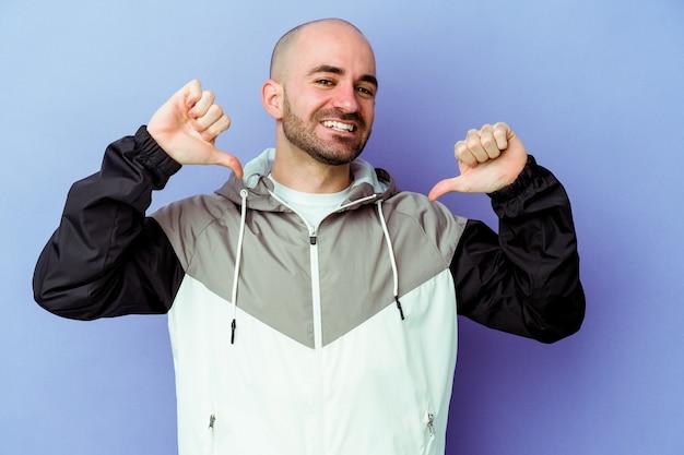 Jeune homme chauve caucasien isolé sur fond violet se sent fier et confiant, exemple à suivre.