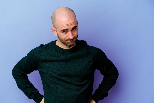 Jeune homme chauve caucasien isolé sur fond violet souffle les joues, a une expression fatiguée. concept d'expression faciale.