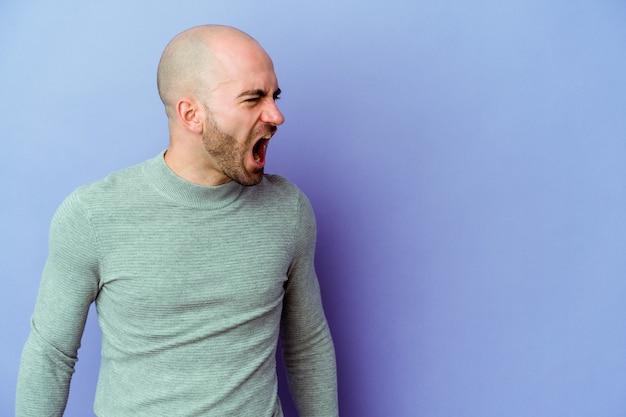 Jeune homme chauve caucasien isolé sur mur violet criant très en colère, concept de rage, frustré.