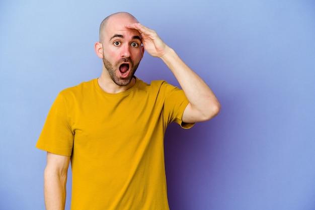 Jeune homme chauve caucasien isolé sur un mur violet crie fort, garde les yeux ouverts et les mains tendues.