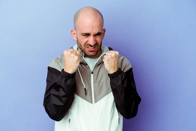 Jeune homme chauve caucasien isolé sur mur violet montrant le poing, expression faciale agressive.