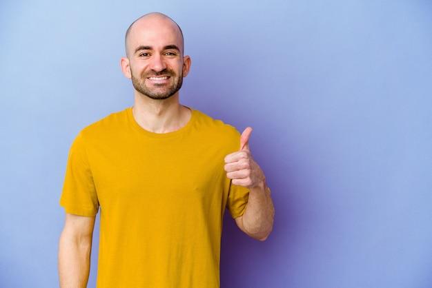 Jeune homme chauve caucasien isolé sur mur violet souriant et levant le pouce vers le haut