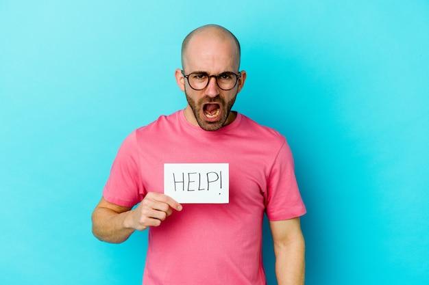 Jeune homme chauve caucasien tenant une pancarte d'aide isolée sur un mur violet criant très en colère et agressif.