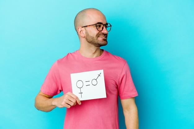 Jeune homme chauve caucasien tenant une pancarte d'égalité des sexes isolée sur un mur jaune regarde de côté souriant, gai et agréable.