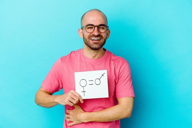 Jeune homme chauve caucasien tenant une pancarte d'égalité des sexes isolée