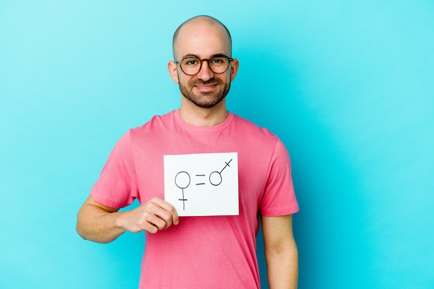 Jeune homme chauve caucasien tenant une pancarte d'égalité des sexes sur jaune heureux, souriant et joyeux.