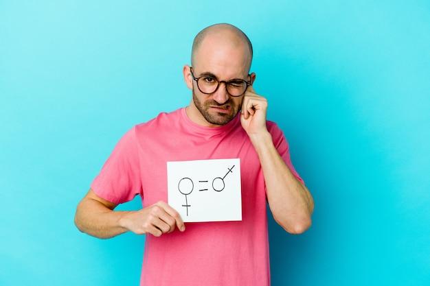 Jeune homme chauve caucasien tenant une pancarte d'égalité des sexes sur les oreilles couvrant jaune avec les mains.