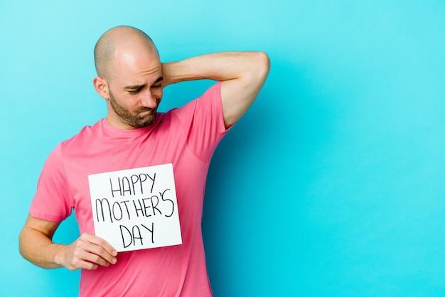 Jeune homme chauve caucasien tenant une pancarte de fête des mères heureuse isolée sur fond bleu touchant l'arrière de la tête, pensant et faisant un choix.