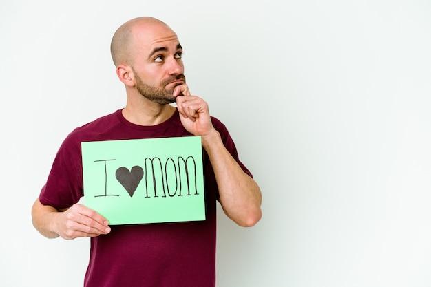 Jeune homme chauve caucasien tenant une pancarte i love maman isolée sur fond jaune regardant de côté avec une expression douteuse et sceptique.