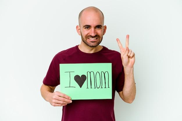 Jeune homme chauve caucasien tenant une pancarte j'aime maman isolée sur fond jaune montrant le numéro deux avec les doigts.