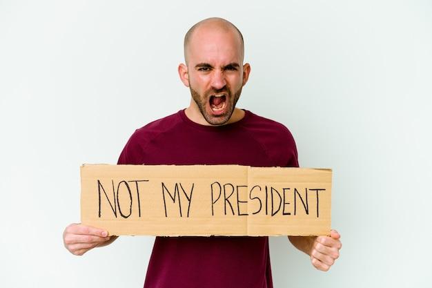 Jeune homme chauve caucasien tenant une pancarte pas mon président isolé sur fond blanc criant très en colère et agressif.