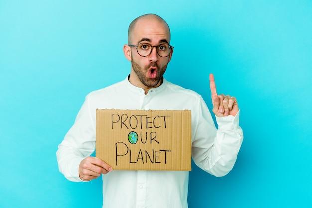Jeune homme chauve caucasien tenant une pancarte protéger notre planète isolée sur fond violet ayant une excellente idée, concept de créativité.