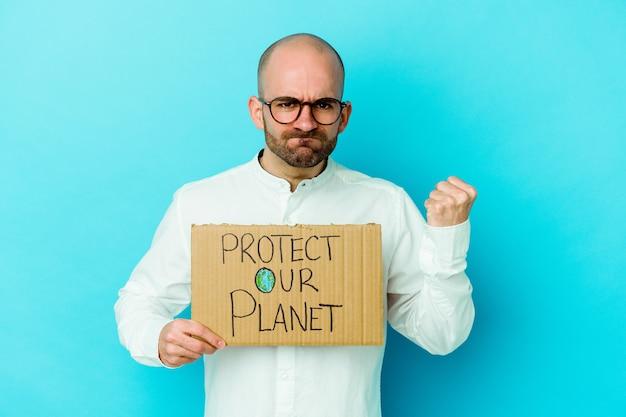 Jeune homme chauve caucasien tenant une pancarte protéger notre planète isolée sur un mur violet montrant le poing à la caméra, expression faciale agressive.