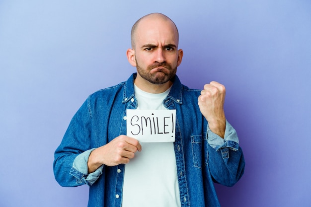 Jeune homme chauve caucasien tenant une pancarte de sourire isolée sur un mur violet montrant le poing à la caméra, expression faciale agressive.