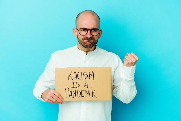 Jeune homme chauve caucasien tenant un racisme est une pandémie isolée sur un mur blanc montrant le poing, une expression faciale agressive.