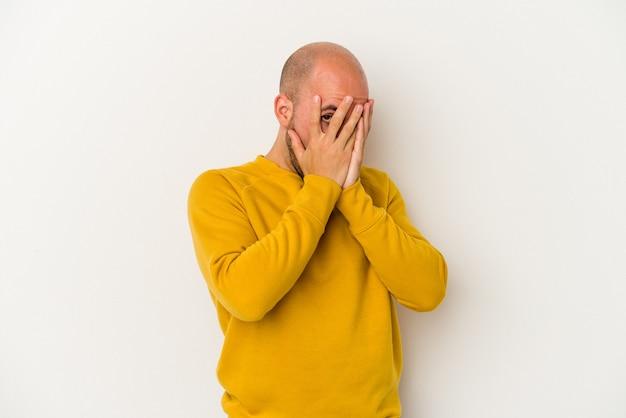 Jeune homme chauve isolé sur fond blanc clignote à travers les doigts effrayés et nerveux.