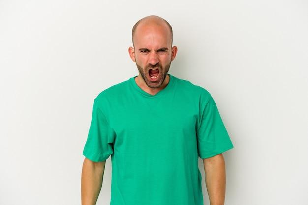 Jeune homme chauve isolé sur fond blanc criant très en colère, concept de rage, frustré.