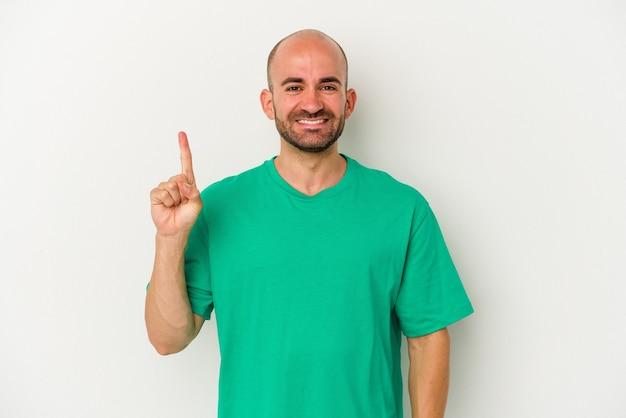 Jeune homme chauve isolé sur fond blanc montrant le numéro un avec le doigt.