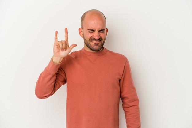 Jeune homme chauve isolé sur fond blanc montrant rock geste avec les doigts