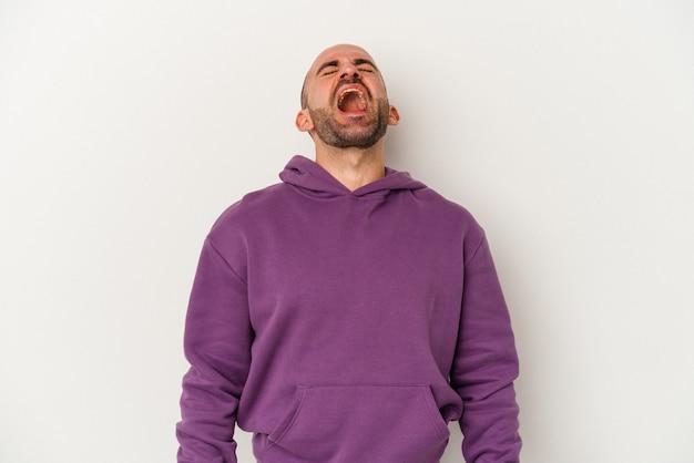 Jeune homme chauve isolé sur fond blanc riant détendu et heureux, cou tendu montrant les dents.