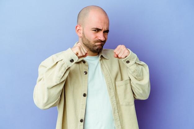 Jeune homme chauve mur isolé jetant un coup de poing, la colère, les combats en raison d'une dispute, la boxe