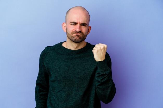 Jeune homme chauve mur isolé montrant le poing à l'avant, expression faciale agressive