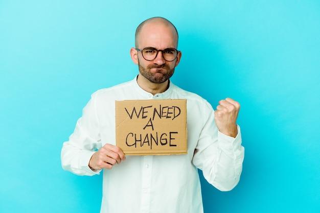 Jeune homme chauve de race blanche tenant un nous avons besoin d'une pancarte de changement isolée sur un mur violet montrant le poing à l'avant, expression faciale agressive