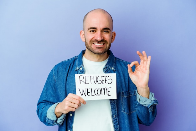 Jeune homme chauve de race blanche tenant une pancarte de bienvenue de réfugiés isolé sur un mur bleu joyeux et confiant montrant le geste ok