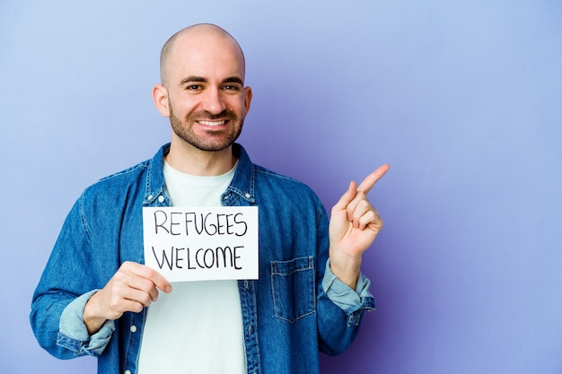 Jeune homme chauve de race blanche tenant une pancarte de bienvenue de réfugiés isolé sur un mur bleu souriant et pointant de côté, montrant quelque chose à l'espace vide