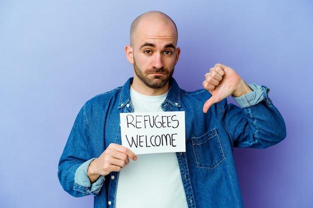 Jeune homme chauve de race blanche tenant une pancarte de bienvenue des réfugiés isolée sur fond bleu montrant un geste d'aversion, les pouces vers le bas. notion de désaccord.