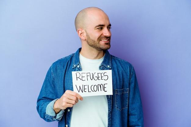 Jeune homme chauve de race blanche tenant une pancarte de bienvenue des réfugiés isolée sur le mur bleu regarde de côté souriant, gai et agréable