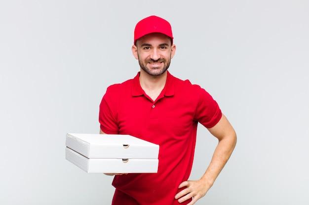 Jeune homme chauve souriant joyeusement avec une main sur la hanche et une attitude confiante, positive, fière et amicale
