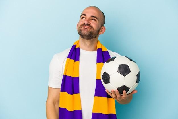 Jeune homme chauve sportif portant une écharpe isolée sur fond bleu rêvant d'atteindre des objectifs et des buts