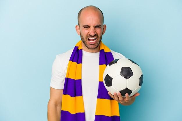 Jeune homme chauve sportif portant un foulard isolé sur fond bleu criant très en colère et agressif.