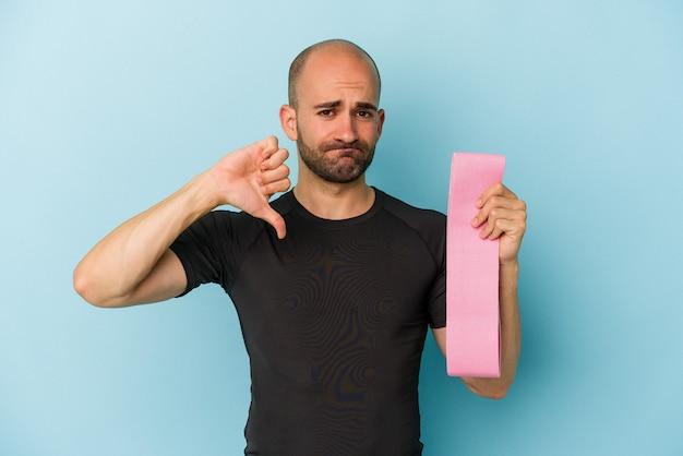 Jeune homme chauve sportif tenant une bande élastique isolée sur fond bleu montrant un geste d'aversion, les pouces vers le bas. notion de désaccord.
