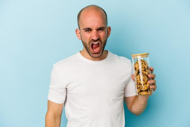 Jeune homme chauve tenant des cookies isolés sur fond bleu criant très en colère et agressif.