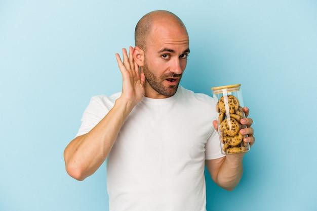 Jeune homme chauve tenant des cookies isolés sur fond bleu essayant d'écouter un potin.