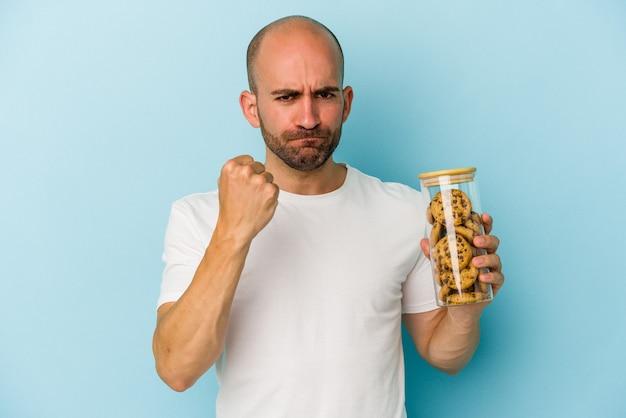 Jeune homme chauve tenant des cookies isolés sur fond bleu montrant le poing à la caméra, expression faciale agressive.
